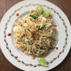 a white plate with Pad Thai